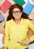 Smiling female student in eyeglasses with pencil Stock Photo