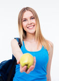 Smiling female student holding green apple Royalty Free Stock Photos