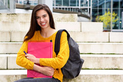 Smiling female student holding notebook and pen Royalty Free Stock Photo