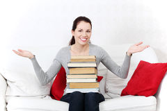 Smiling female student holding a pile of books. Stock Photography