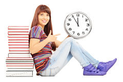 Smiling female student leaning on a pile of books and pointing Royalty Free Stock Photo