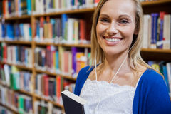 Smiling female student listening to music in the library Stock Photo