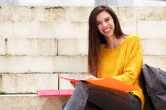 Smiling female student with notebook and pen Stock Photos