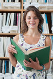 Smiling female student with a open book against bookshelf in library Royalty Free Stock Image