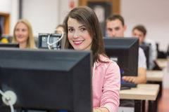 Smiling female student with others in the computer room Stock Images