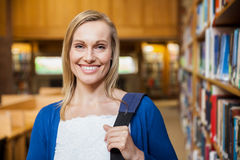 Smiling female student posing in the library Royalty Free Stock Photography