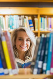 Smiling female student reading book in the library Royalty Free Stock Image