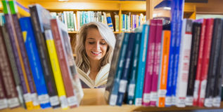 Smiling female student reading book in the library Stock Photography