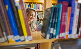 Smiling female student reading book in the library Stock Image
