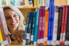 Smiling female student selecting book in the library Stock Image