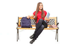 Smiling female student sitting on bench and holding a notebook Stock Photos