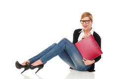 Smiling female student sitting on the floor with ring binder. Royalty Free Stock Photos