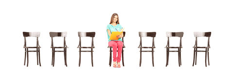 Smiling female student sitting on a wooden chair and writing not. Es, isolated on white background Stock Photos