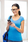 Smiling female student with smartphone and bag Royalty Free Stock Images