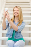 Smiling female student with smartphone Royalty Free Stock Images