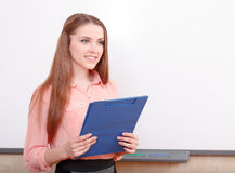 Smiling female student standing with folder Stock Photography