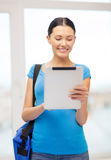 Smiling female student with tablet pc and bag Royalty Free Stock Photo