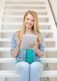 Smiling female student with tablet pc computer Stock Photography