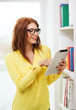 Smiling female student with tablet pc in library Royalty Free Stock Photography
