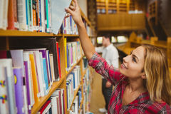 Smiling female student taking book Stock Photo