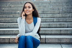Smiling female student talking on the phone outdoors Stock Photography