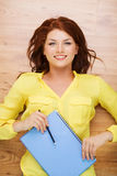 Smiling female student with textbook and pencil Stock Images