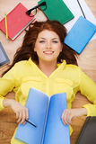 Smiling female student with textbook and pencil. Education and home concept - smiling redhead female student lying on floor with textbook and pencil Stock Photo