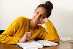 Smiling female student thinking with with pen and paper Royalty Free Stock Photography