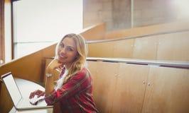 Smiling female student using laptop Royalty Free Stock Photo