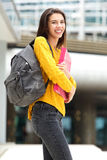 Smiling female student walking to class with bag and books Stock Image
