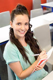 Smiling female student writing notes in classroom Stock Photos