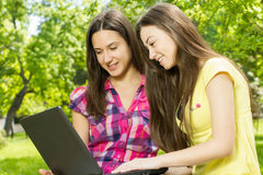 Smiling female students using laptop Royalty Free Stock Image