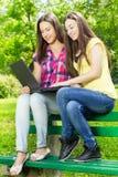 Smiling female students using laptop Royalty Free Stock Photo