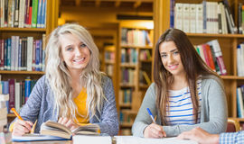 Smiling female students writing notes at library desk Royalty Free Stock Photos