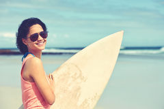 Smiling female surfer. Portrait of happy young woman with surfboard at the beach Royalty Free Stock Image