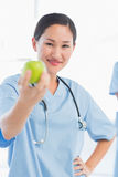 Smiling female surgeon holding out an apple in hospital Stock Photography