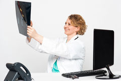 Smiling female surgeon looking at patients x-ray Stock Photography