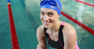 Smiling female swimmer sitting by pool