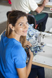 Smiling Female Tailor Cutting Fabric At Workbench Stock Photo