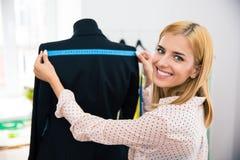 Smiling female tailor measuring tape jacket Royalty Free Stock Photos