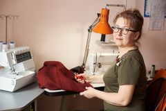 Smiling female tailor on sewing process of skirt, holding scissors. Overlock and sewing-machine on background. Side view. Needlewoman seamstress in glasses royalty free stock photography