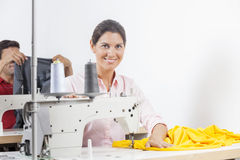 Smiling Female Tailor Sitting At Workbench. Portrait of smiling female tailor sitting at working in sewing factory Royalty Free Stock Photo