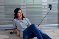 Smiling female taking selfie. Shot of smiling woman in trendy clothes with headphones taking selfie laying down skateboard Stock Photos