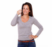 Smiling female talking on cellphone looking at you Stock Image