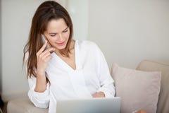 Smiling female talking on phone browsing web Stock Image