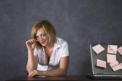 Smiling female teacher with closed eyes dreams of vacation in school office stock photo