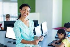 Smiling female teacher using laptop. Portrait of smiling female teacher using laptop during computer class Stock Photo