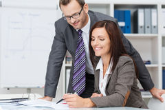 Smiling female team leader. Manageress or businesswoman showing paperwork to her male business colleague or partner as they discuss their strategy Royalty Free Stock Photos
