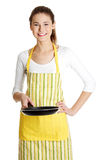 Smiling female teen with a frying pan. stock images