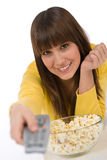 Smiling female teenager watching television Royalty Free Stock Photography